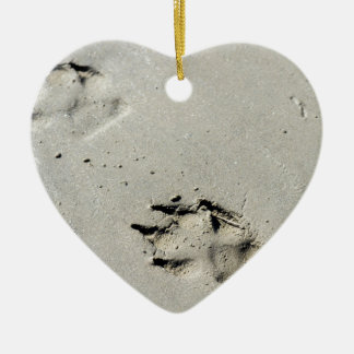 Large dog's paw prints on wet sand ceramic ornament