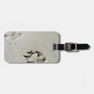 Large dog's paw prints on wet sand luggage tag