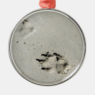 Large dog's paw prints on wet sand metal ornament