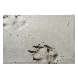 Large dog's paw prints on wet sand placemat