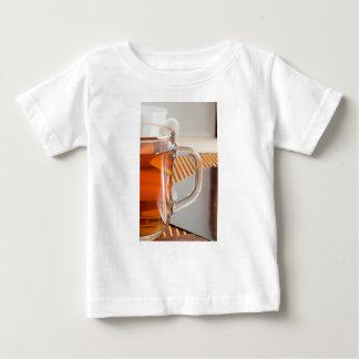 Large transparent glass mug with tea close up baby T-Shirt