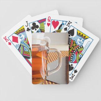 Large transparent glass mug with tea close up bicycle playing cards