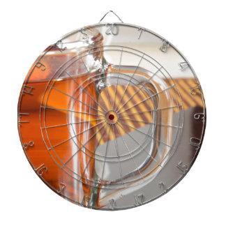 Large transparent glass mug with tea close up dartboard