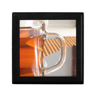 Large transparent glass mug with tea close up gift box