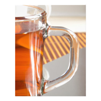 Large transparent glass mug with tea close up letterhead