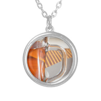 Large transparent glass mug with tea close up silver plated necklace