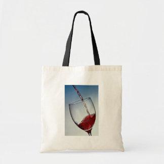 Le vin rouge a versé dans le verre de vin sac en toile budget