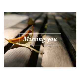 Leaf on wooden bench missing you postcard