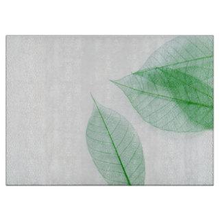 Leaf skeletons on white cutting board