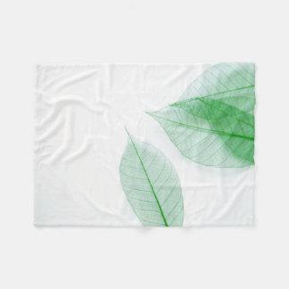 Leaf skeletons on white fleece blanket
