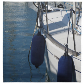 Left side of sailing boat with two blue fenders napkin