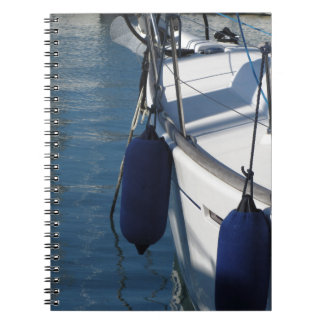 Left side of sailing boat with two blue fenders notebooks