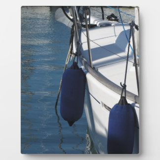 Left side of sailing boat with two blue fenders plaque