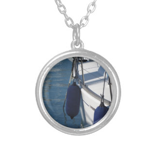 Left side of sailing boat with two blue fenders silver plated necklace