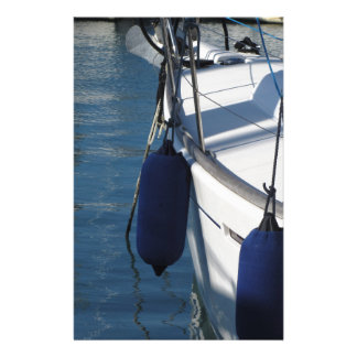 Left side of sailing boat with two blue fenders stationery