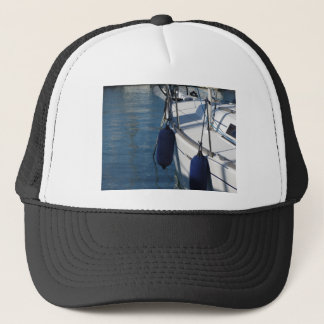 Left side of sailing boat with two blue fenders trucker hat