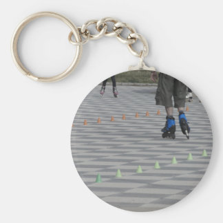 Legs of guy on inline skates . Inline skaters Keychain