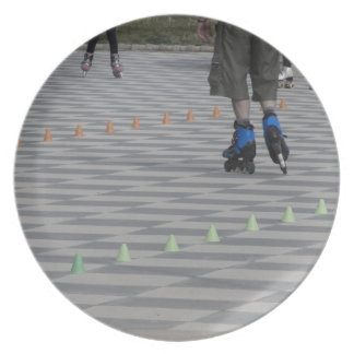 Legs of guy on inline skates . Inline skaters Plate