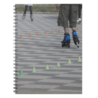Legs of guy on inline skates . Inline skaters Spiral Note Book