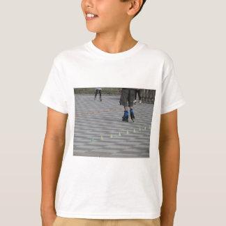 Legs of guy on inline skates . Inline skaters T-Shirt