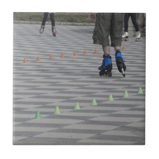 Legs of guy on inline skates . Inline skaters Tile