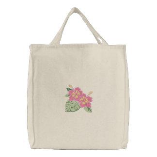 Les fleurs jaunes roses de ketmie ont brodé le sac