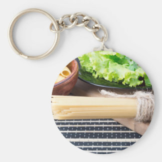 Lettuce in a black plate, pasta in a wooden bowl keychain