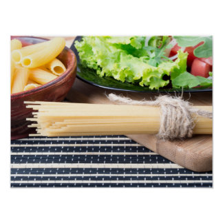 Lettuce in a black plate, pasta in a wooden bowl poster