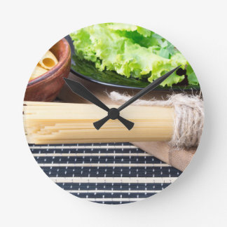 Lettuce in a black plate, pasta in a wooden bowl round clock