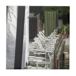 Line of closed beach chairs and umbrellas tile