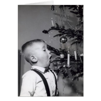 Little boy blows out candle on Christmas tree Card