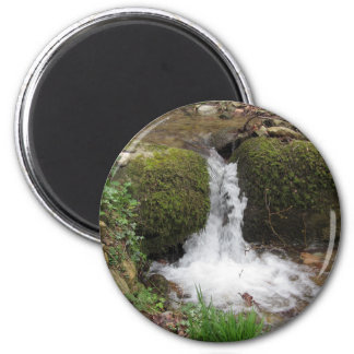 Little waterfall by mossy rocks in the forest magnet