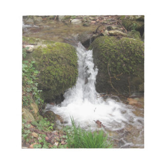 Little waterfall by mossy rocks in the forest notepad