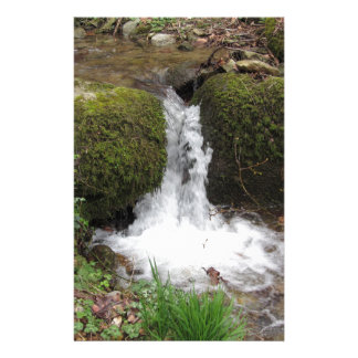 Little waterfall by mossy rocks in the forest stationery
