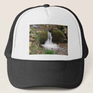 Little waterfall by mossy rocks in the forest trucker hat