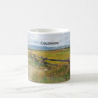 log fence by a prairie coffee mug