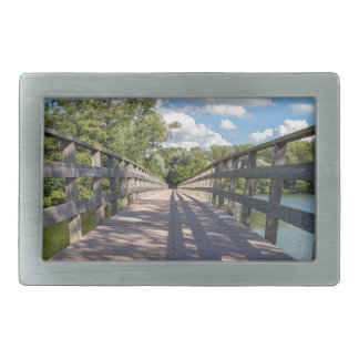 Long wooden bridge over water of pond belt buckles