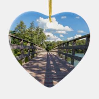 Long wooden bridge over water of pond ceramic heart ornament