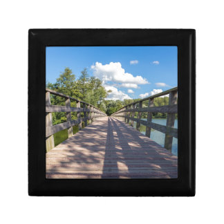 Long wooden bridge over water of pond gift box