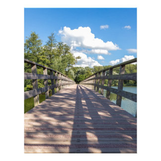 Long wooden bridge over water of pond letterhead