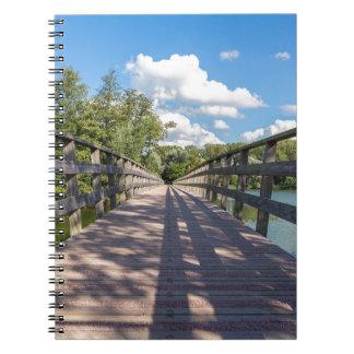 Long wooden bridge over water of pond notebook