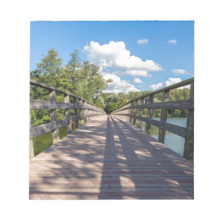 Long wooden bridge over water of pond notepads