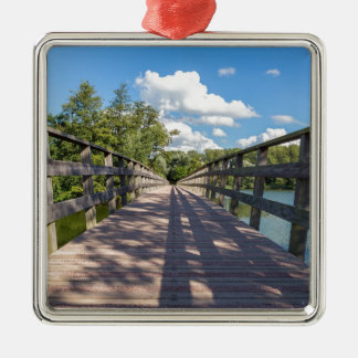 Long wooden bridge over water of pond Silver-Colored square ornament
