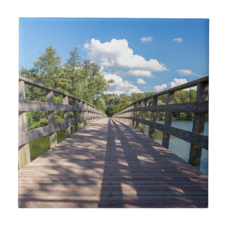 Long wooden bridge over water of pond tile