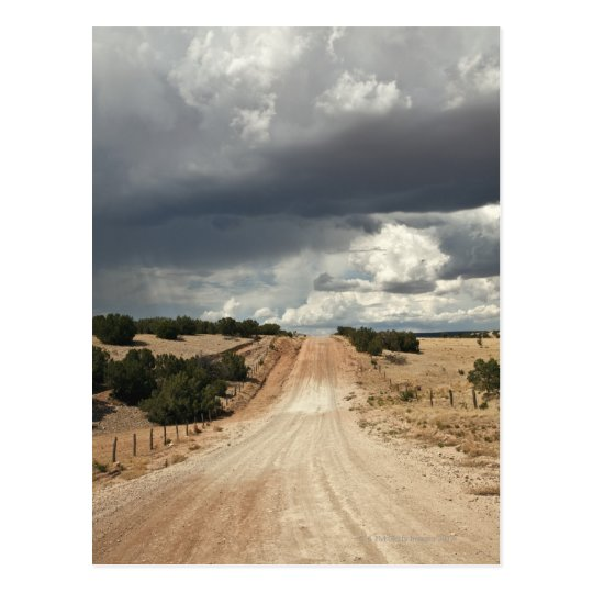 Looking down a  dirt country road in NM with Postcard