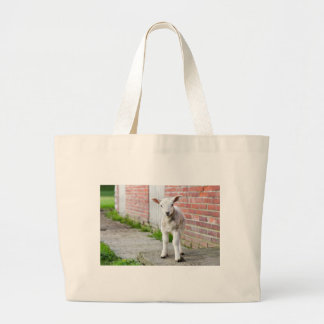 Looking lamb stands near brick wall large tote bag