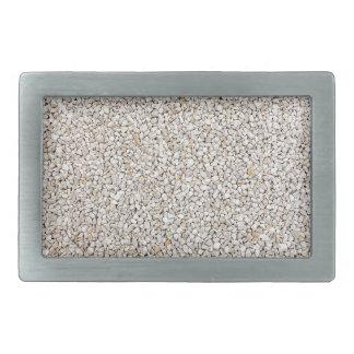 Lot of grey gravel stones as background rectangular belt buckle