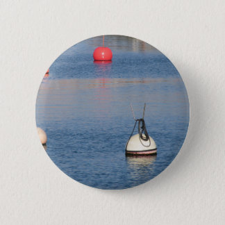 Lots of mooring buoys floating on calm sea water 2 inch round button