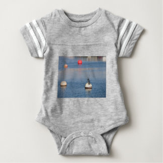 Lots of mooring buoys floating on calm sea water baby bodysuit