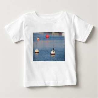 Lots of mooring buoys floating on calm sea water baby T-Shirt
